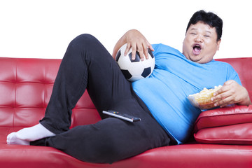 Overweight man watching football match 1