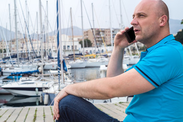 businessman talking on the phone close to the luxurious harbor