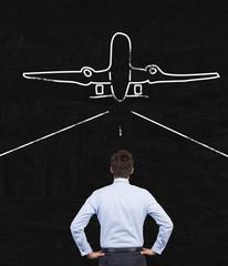 businessman looking at airplane