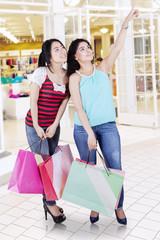 Two women shopping in modern mall