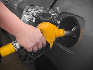 Pumping gas at gas pump.