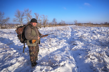 Hunter on field waiting victim. Winter hunting.