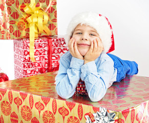 Charming little boy lying on present