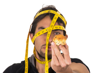 handsome athletic young man wrapped around measuring tape