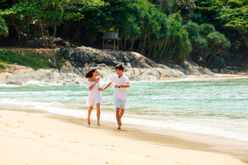 happy couple running on tropical beach