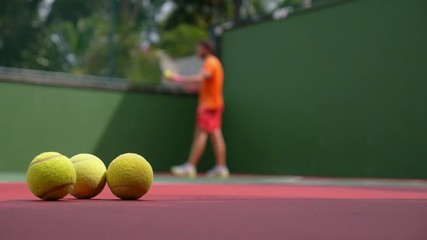 Tennis Player Playing on Court with Tennis Balls.
