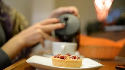 Close-up. Girl eats tartlet with raspberries in a bar, restauran