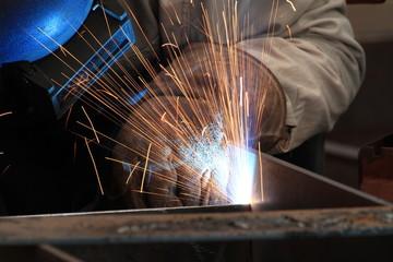 MIG welder welding steel part with all safety equipment