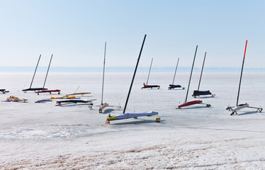 Ice boats in protective covers on ice of frozen Lake Baikal