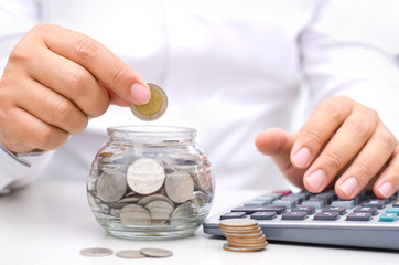 Male hand putting money coins into glass jar bank