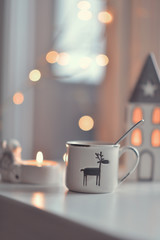 on the window sill at the window lit candle, a house, a cup with