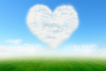 Heart cloud on blue sky and green field