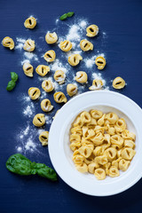 Raw tortellini with dough, above view, studio shot