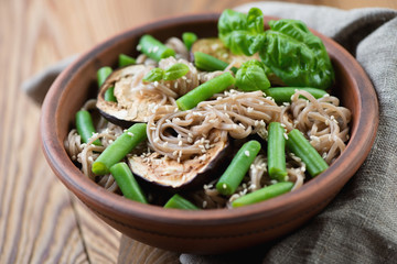 Soba noodles with aubergine slices and beans, close-up