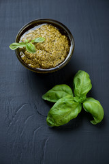 Freshly made pesto sauce over black wooden background, close-up