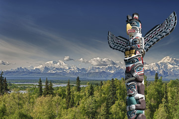 A totem wood pole in mountain background