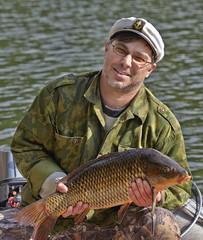 Fisherman holding a fish carp