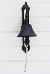 Brass bell on white wood wall.