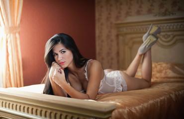 Beautiful sexy brunette young woman wearing white lingerie lying