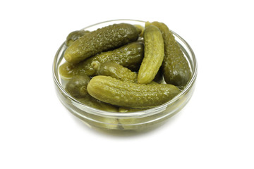 salted cucumbers in a glass container on a white background