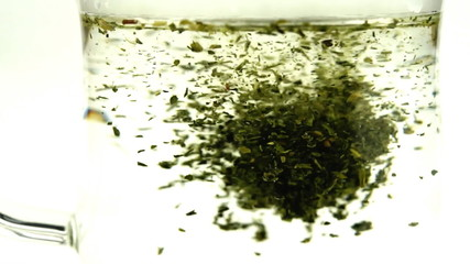 Loose leaf green tea dissolving in hot water in slow motion