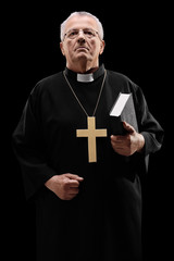 Mature male priest holding a holy bible