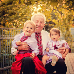 Grandparents with grandchildren in Ukrainian costume at sunset