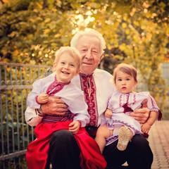 Grandparents with grandchildren in Ukrainian costume at sunset