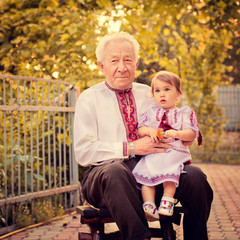 Grandfather with granddaughter in Ukrainian costume at sunset