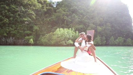 handsome groom hug his beautiful brunette bride sitting on boat