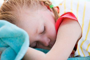 Adorable little girl at beach sleeping