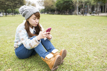 Attractive young Asian woman using smartphone, closeup portrait.