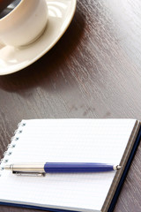 A cup of coffee and a notebook with a pen on a wooden table