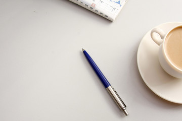 A cup of coffee and a pen on the table, closeup