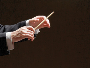 Concert conductor hands with a baton isolated on a black