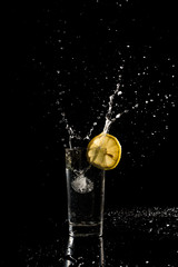 Water splashing out of a glass as an ice cube is dropped in to a