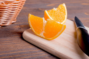 sliced ripe appetizing delicious orange on cutting board next to