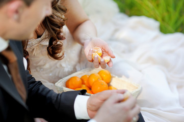 Young bride and groom eating tangerines