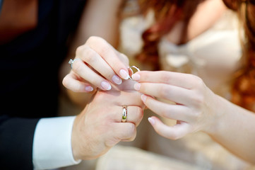 Bride and groom holding their wedding rings