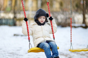 Adorable girl having fun on a swing on winter day