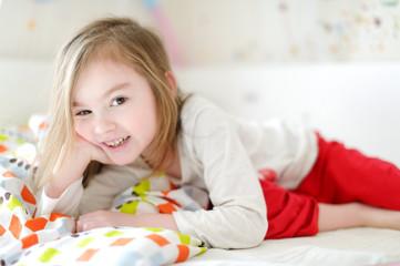 Little girl in bed on sunny morning