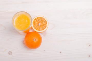 orange juice beside delicious ripe oranges on the table