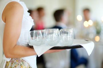 Waitress holding a dish of glasses