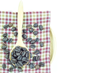 coffee beans in wooden spoon on a tablecloth on white background