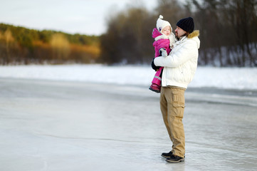 Young father and his daughter on winter day