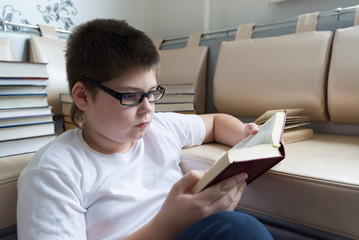 Boy with glasses reading a book in  room