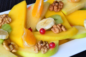 Salad of fruit with mango,walnuts,oranges,kiwi,bananas,apples