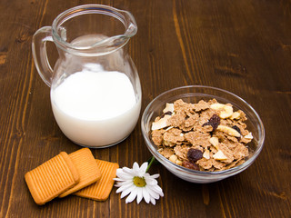 Jug of milk and cereal in bowl on wooden table