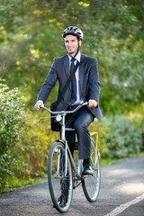 Full length of young businessman riding a bicycle