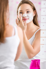 Young cute girl putting facial mask on her face